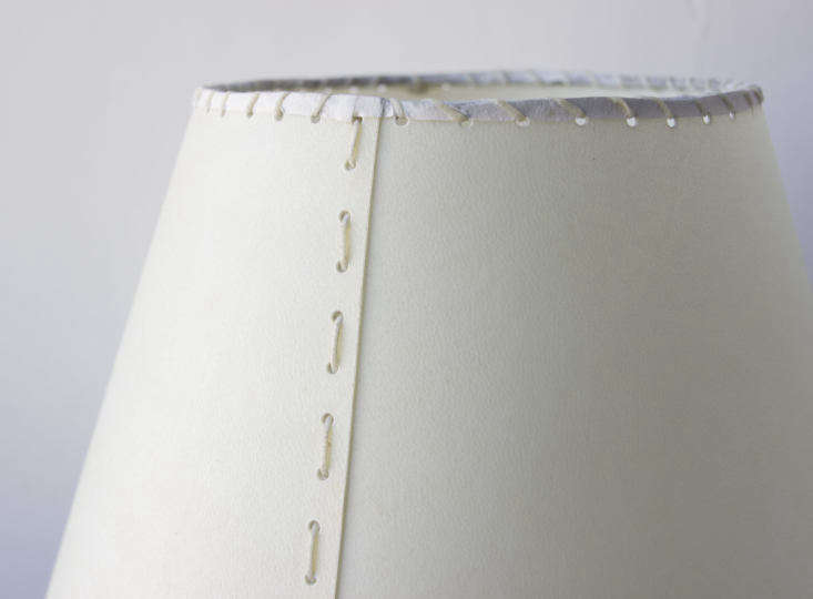 The lampshade has a hand-stitched cream goatskin parchment shade and a hand-dyed braided cotton cord.