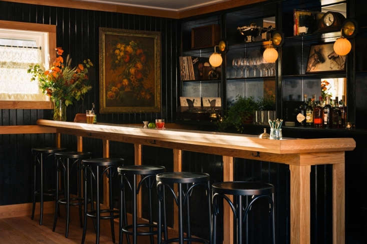 Inside the lobby, dark-painted cladding surrounds the bar for dramatic effect.