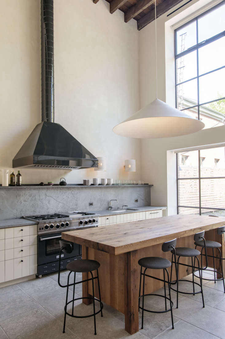 An oversized pendant above the island matches the grand quality of the double-height kitchen. (Oversized pendant lights are one of the loading=