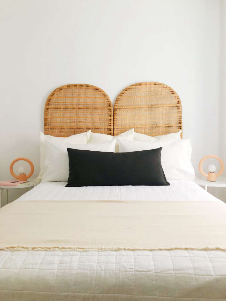 The Hoveys furnished a bedroom in the same apartment with an Ikea limited-edition rattan headboard and Urban Outfitters Ayo Ceramic Table Lamps—both since discontinued. The Belgian Linen Quilt, $9, is from West Elm and the dark gray Linon Pillow, $54.95, is from CB