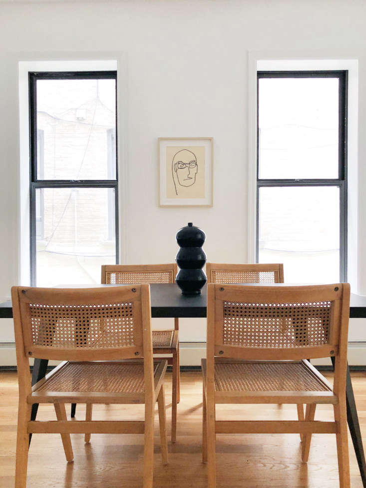 For a Park Slope apartment staged on a tight budget (and sold with a furnishings purchase option), Hollister and Porter went with a palette of black, white, and wood. The rattan and rubberwood Marte Dining Chairs, $9 each, are from Urban Outfitters—&#8