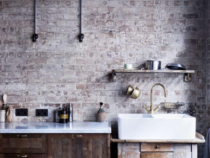 Preserved weathered brick makes for a stylish backsplash in a London loft.