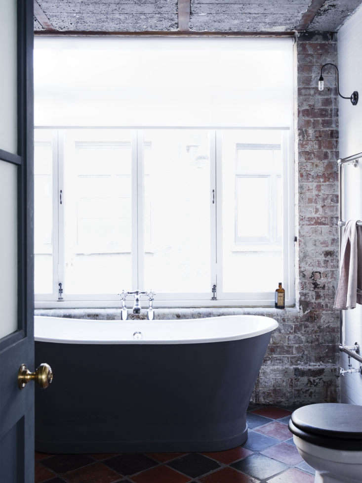 A sleek soaking tub and exposed brick wall create a feeling of laid-back luxury in London.