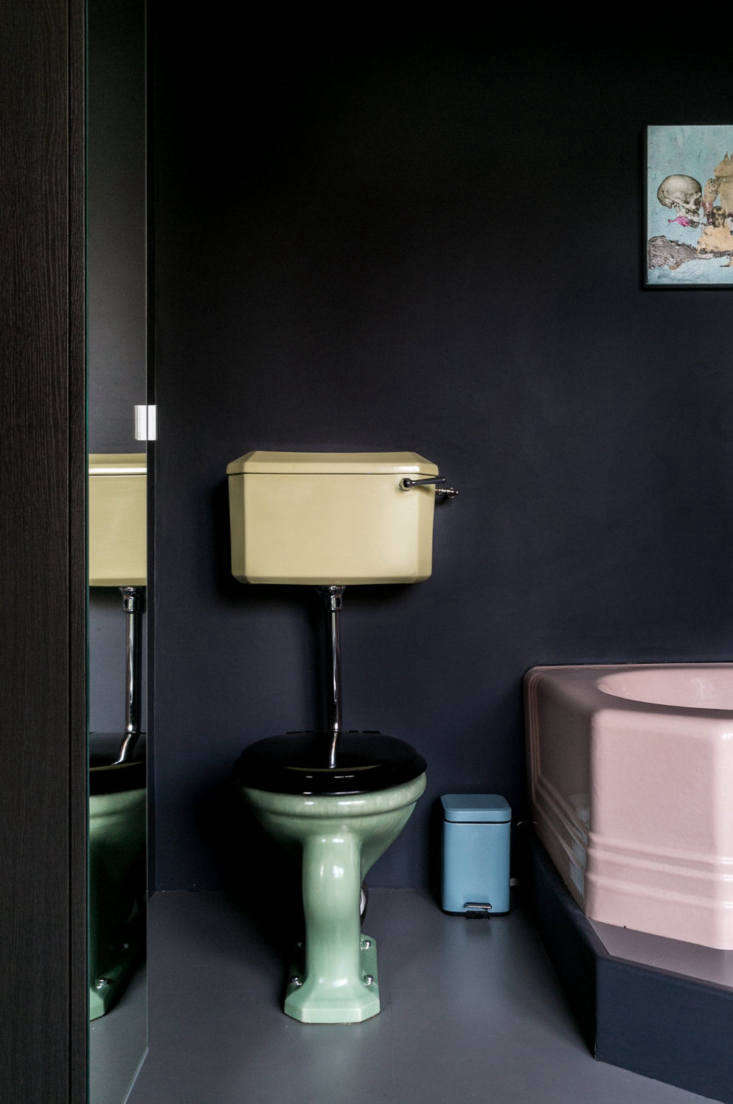 In his Yard House project, Jonathan Tuckey used pastel fixtures against a dark, moody backdrop. Photograph via The Modern House.