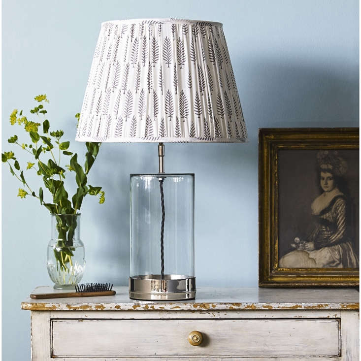 The glass-and-nickel Wisteria Table Lamp from UK lighting company Pooky, £5, comes with dozens of shade options in a range of sizes; this block-printed-cotton Empire Gathered Lampshade starts at £30.