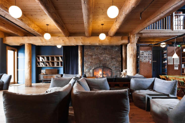 Inside the Lodge are lounging essentials—a large cozy fireplace; comfortable, low pouf seating; and the requisite hipster accessories, a vintage record player and some vinyl. Globe pendant lights are by Schoolhouse.