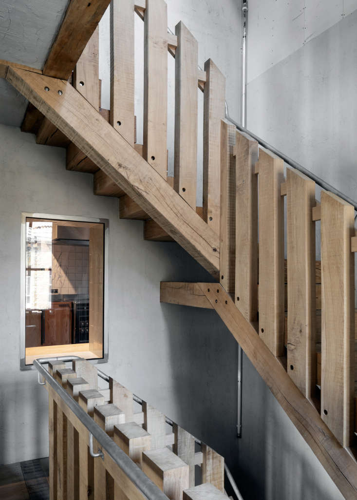 A central oak stair serves as the spine of the building. An oak-framed window on the second floor offers a view into the kitchen atMãos: &#8