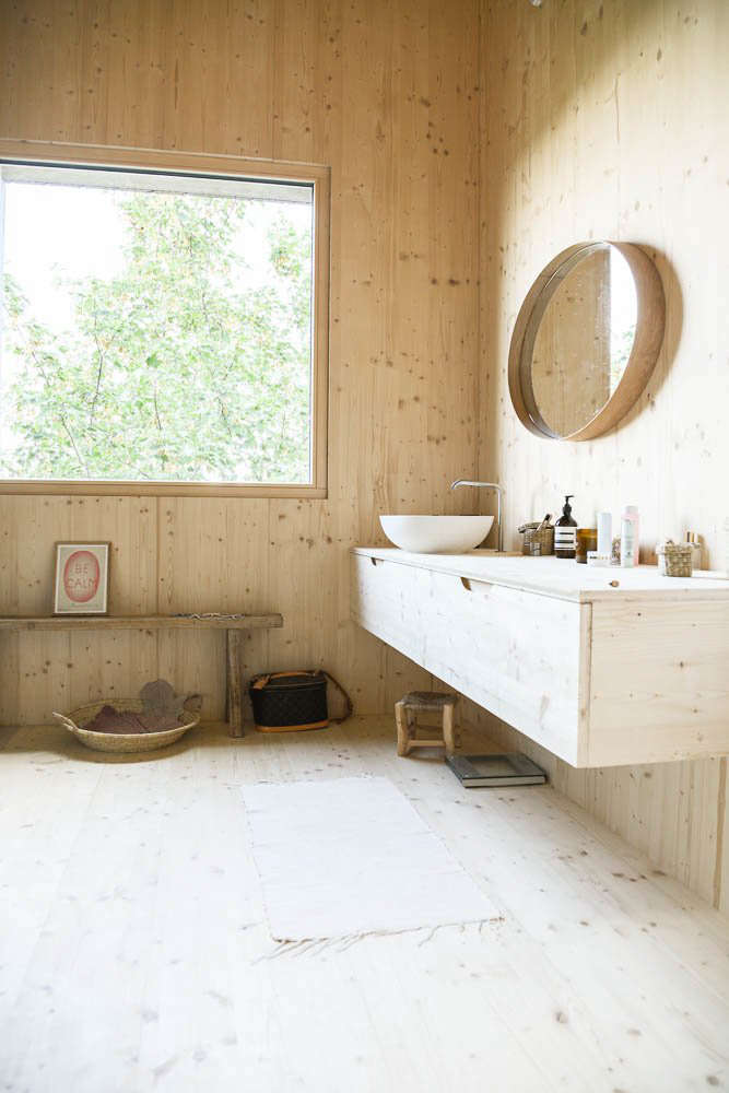 The family bathroom features a round vessel sink with a floating wood console.