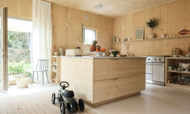 All the cabinets in the kitchen are made of the same wood as the walls and ceilings for a cohesive look. The kitchen is open to the dining and living areas.