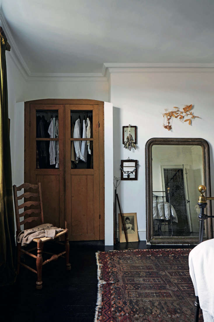 Required Reading An Artist Couples Hauntingly Beautiful Quarters Courtesy of Perfect English Townhouse In the master bedroom, the couple inserted an antique wardrobe into a niche, and leaned a mantel mirror against the wall.