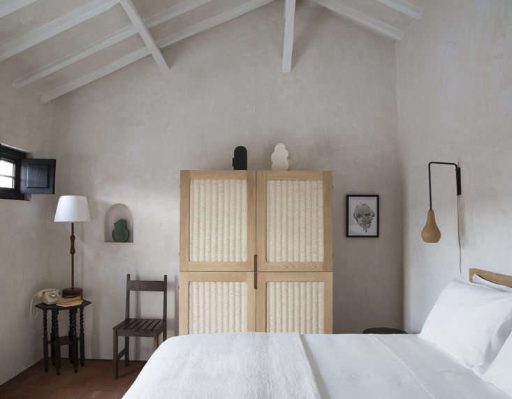 The eight guest bedrooms are coated in plaster, so that even empty walls feel textural. Note the sense of balance here, too, with a pear-shaped sconce weighted against the small black-painted window on the other side of the room, and a chair and tall lamp on either side of a recessed niche.