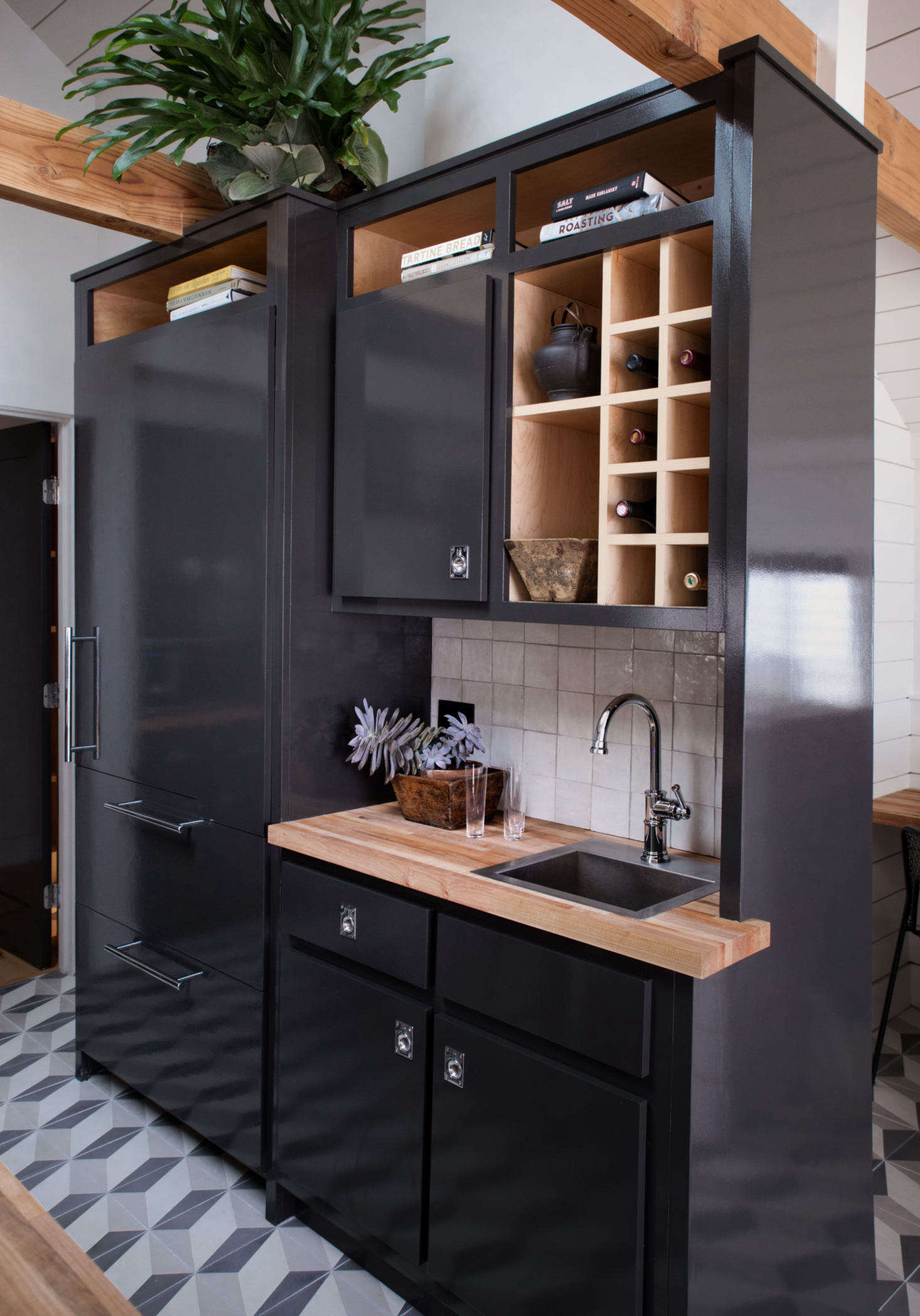 The paneled fridge and bar double as a room divider, and create a study nook and small hall leading to the bath.