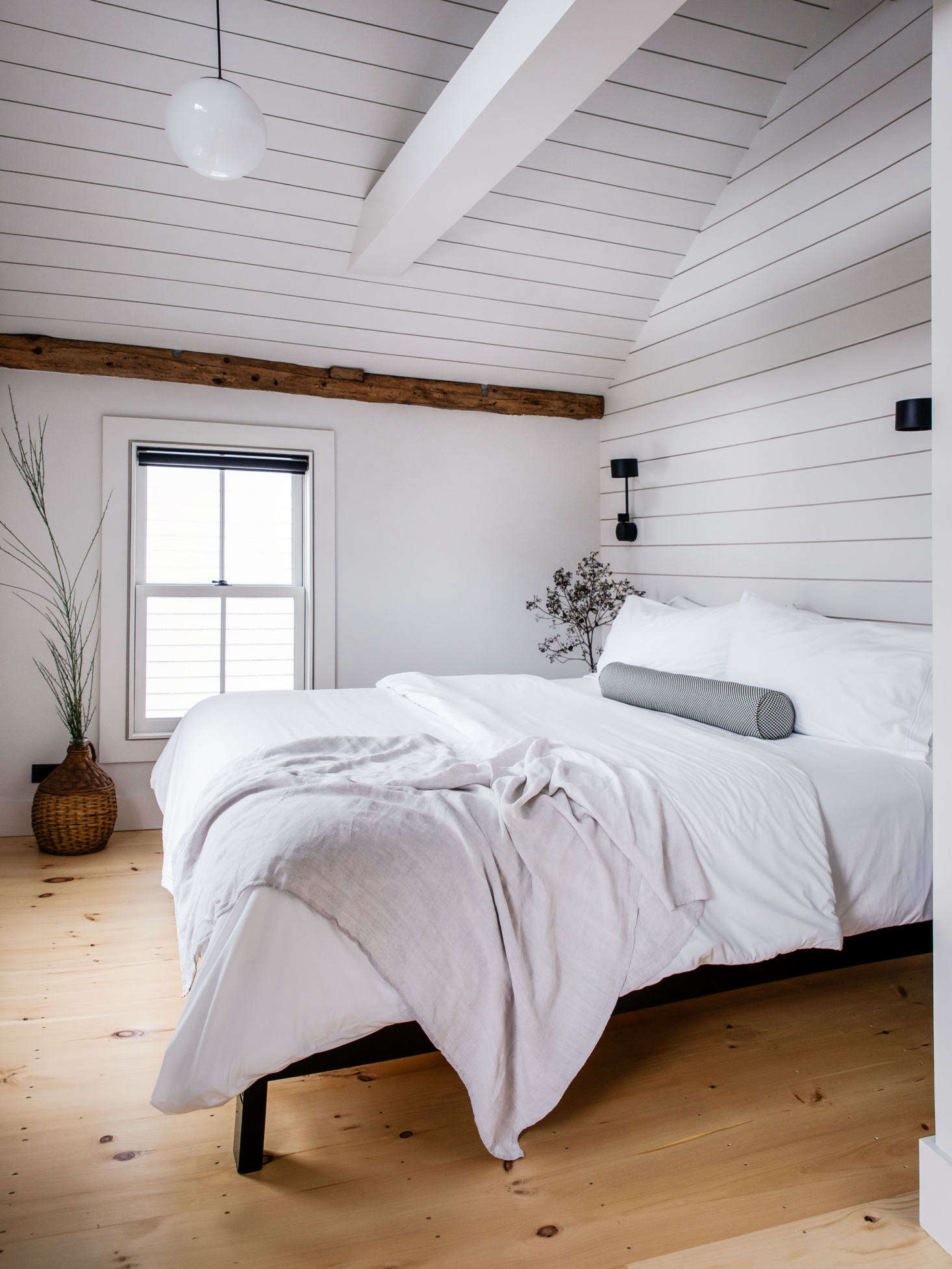 In the upstairs master bedroom, the couple also installed shiplap to accentuate the lofty ceiling. The pendant is Schoolhouse&#8