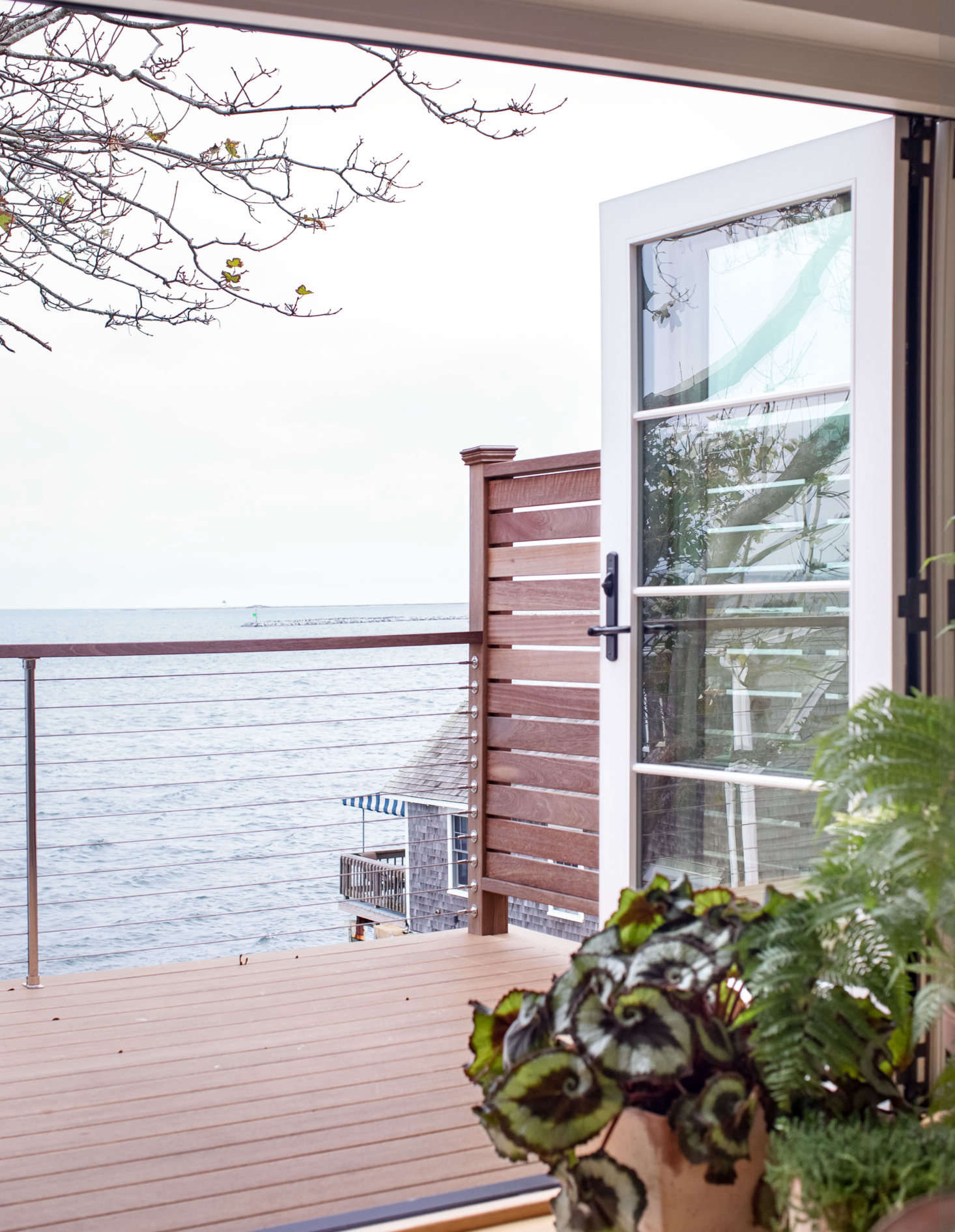 Accordion doors open fully onto the deck, blurring the lines between indoors and out. Here, clean marine accents like steel cable railings enhance the updated nautical feel.