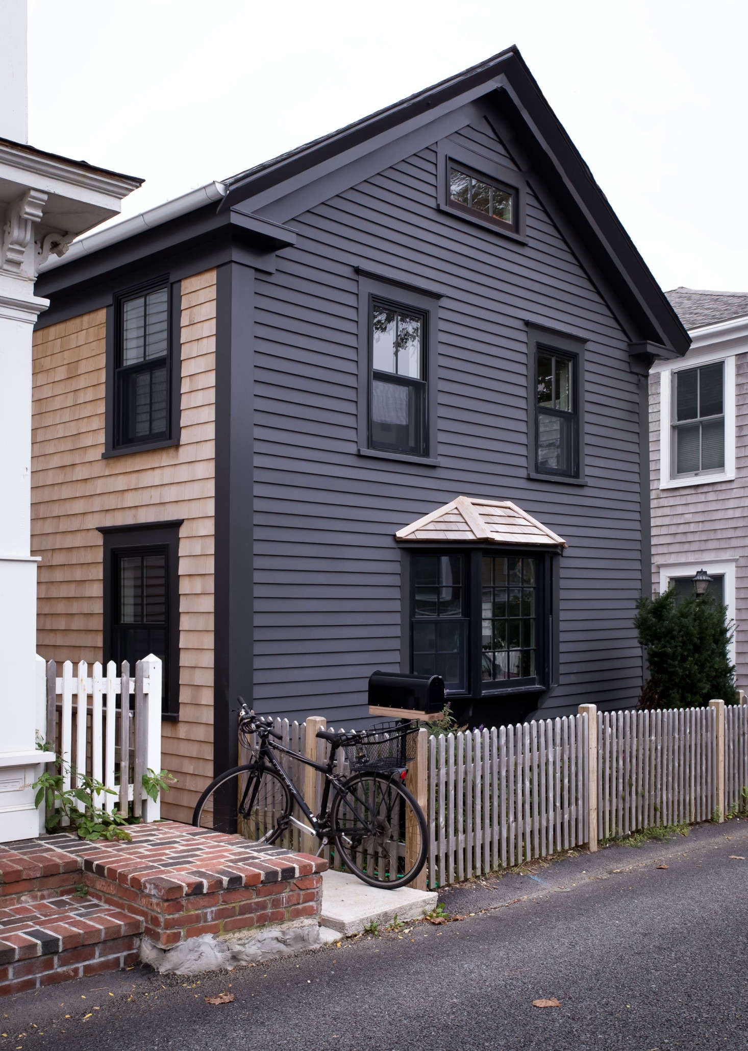 The exterior features traditional shingle and clapboard siding updated with a more modern noir hue: Benjamin Moore&#8
