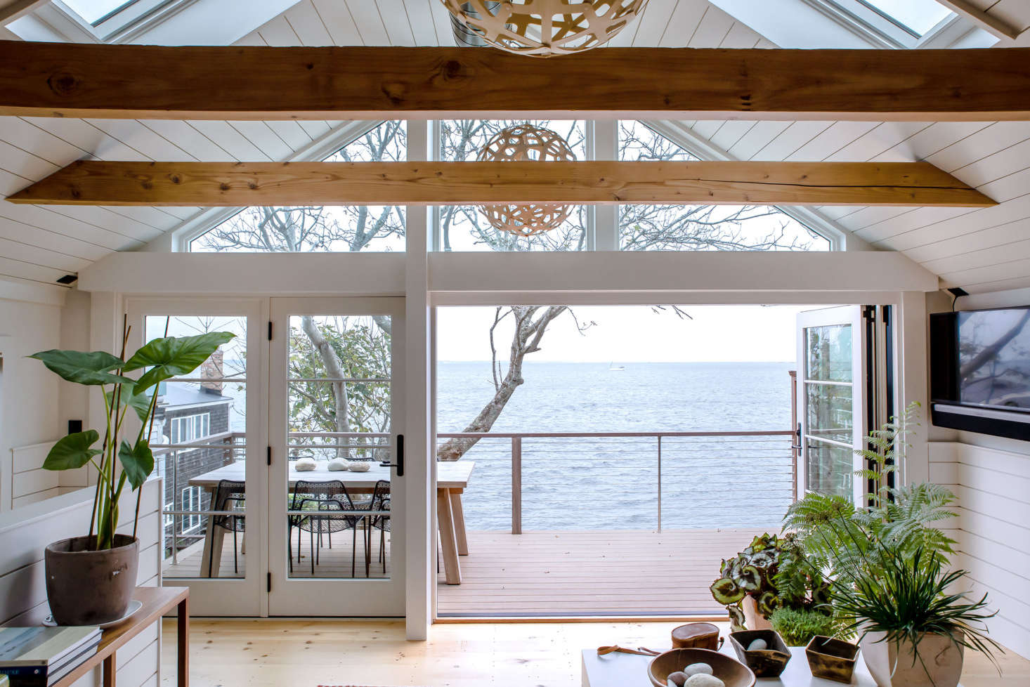 In the open, second-floor living/kitchen space, floor-to-ceiling windows and doors as well as overhead skylights flood the room withsea breezes and sunlight.