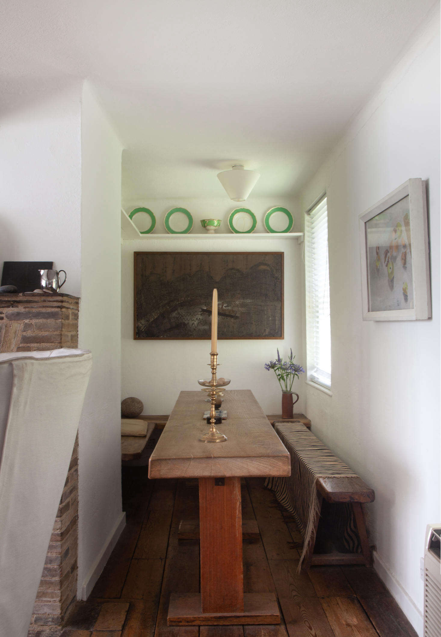 A dining room corner in the original cottage includes a slender table and a textile-draped bench.