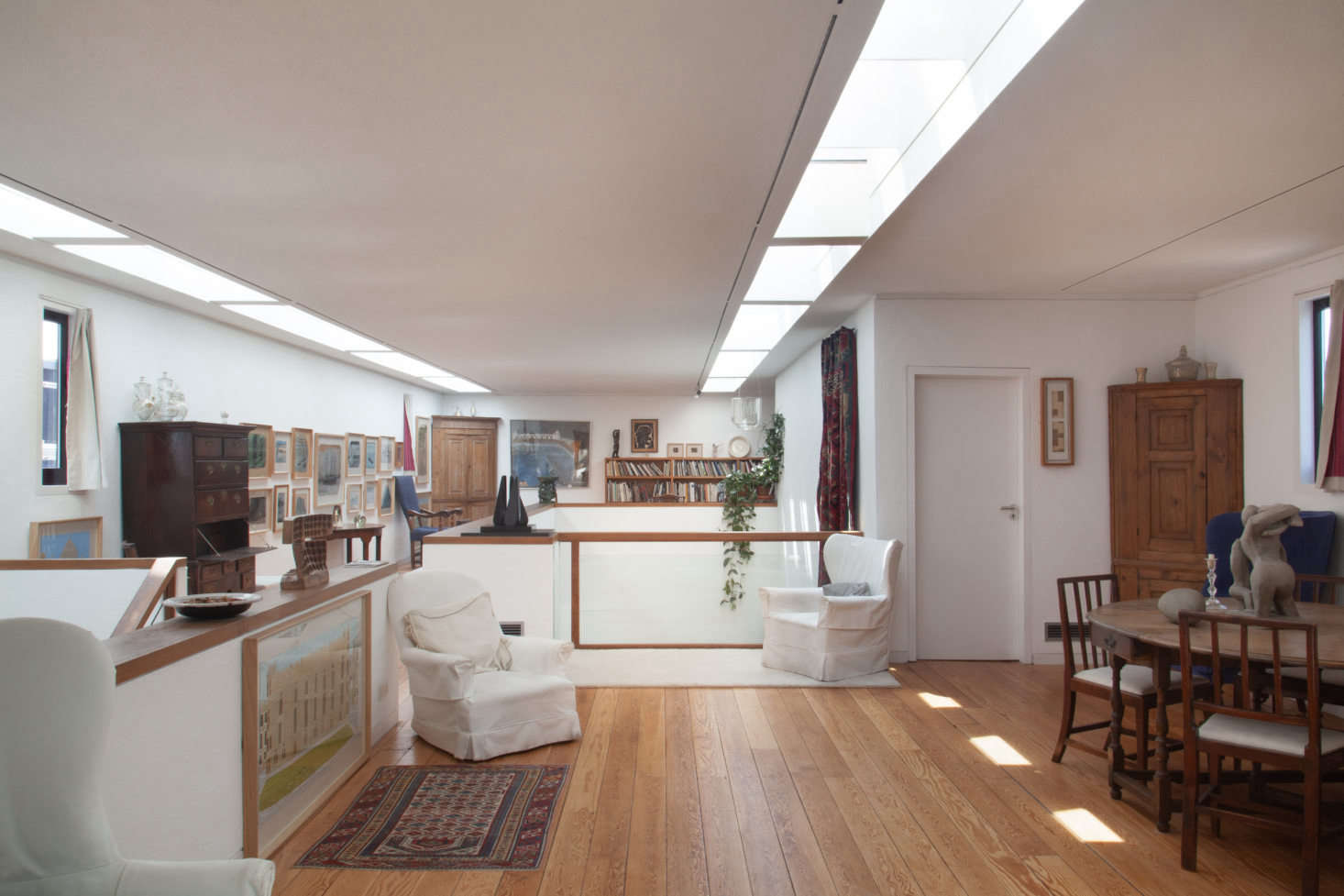 Three slipcovered armchairs are scattered down the length of the second floor modern extension. The furthest chair is tilted for viewing the low-hanging painting beneath the small window, and from the middle chair, the viewer can see Henri Gaudier-Brzeska&#8