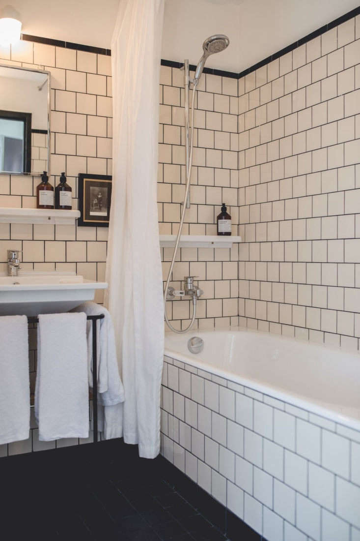 The bathrooms are stylishly detailed with classic (and inexpensive) four-by-four tiles that rise from the floor and extend across the tub. Built-in towel bars surround the sink.