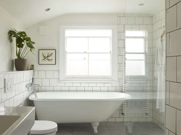 The bath was also fully remodeled, with square white tile sourced from Home Depot and a glass divider by the bath. Surprisingly, the clawfoot bath was not original to the house, but the couple &#8