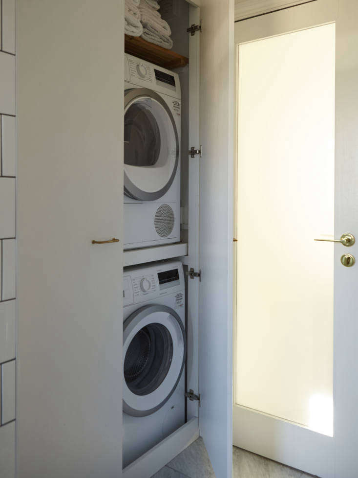 A stacked washer-dryer fits behind double doors.