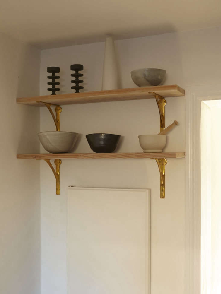High shelves hold sculptural ceramics (and make use of the space above a wall unit).