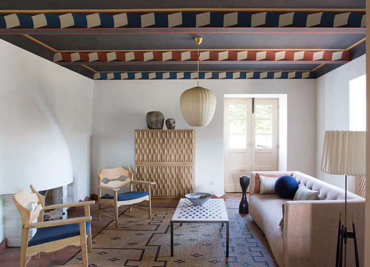 Sculptural Minimalism A Winery Guesthouse by a French Architect in Portugals Douro Valley A living area is a study in balance (sculptural ceiling light, curvaceous fireplace, slim limbed armchairs), color (neutral furniture paired with deep blue grey and rust), and pattern (on the coffee table, armoire, painted geometric ceiling, and the woven straw and leather Tuareg mat, which we included in our post New Directions: \18 Design Trends for \20\18).