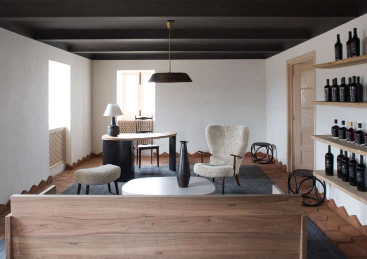 Another living space in a cohesive color palette, with a black-painted ceiling and black rug. The sheepskin chair is Yovanovitch&#8