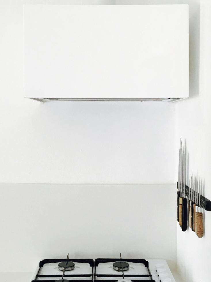 Lessons in Sparseness A Black and White House in Rural Portugal with Echoes of the Shakers In an otherwise austere kitchen, necessary storage doubles as design, as in the knife rack beside the cooktop. The sculptural vent hood cover and the base for the range are both made of thin steel, painted with primer and matte white paint, and made by a local metalworker.