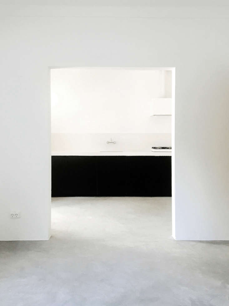 Lessons in Sparseness A Black and White House in Rural Portugal with Echoes of the Shakers A lesson in sparseness: A wide, sculptural doorway leads into the kitchen. Because the interiors are so spartan, Bento chose the limited materials with care: white washed plaster walls and matte concrete floors that have a subtle visual texture.