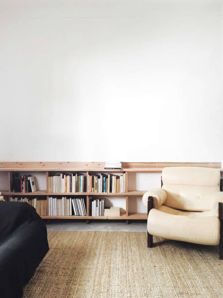 Lessons in Sparseness A Black and White House in Rural Portugal with Echoes of the Shakers In the living area, attention is focused on the lower half of the room, with a simple woven mat and a low, waxed wood bookshelf built into one wall.