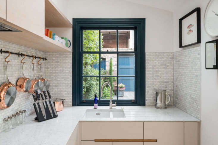marble counters are surrounded by a backsplash of marble mosaic tiles sourced f 15