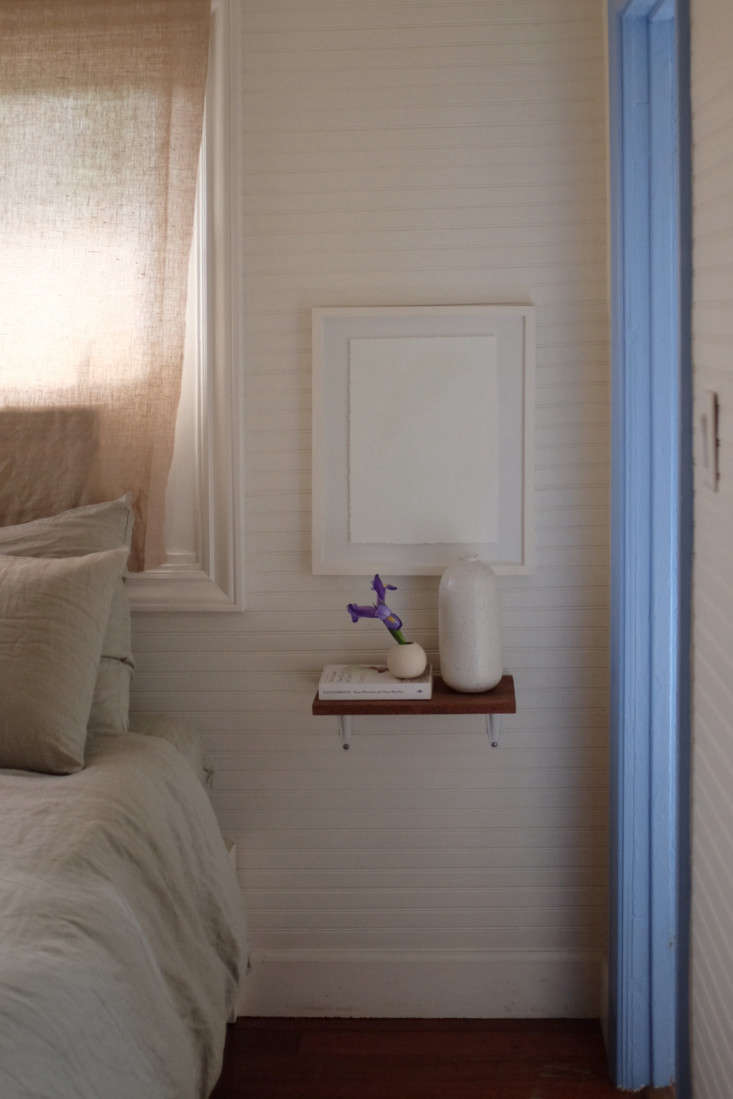 To save space, Alex and Jodi used small shelves in place of nightstands.The bed frame is from Ikea.