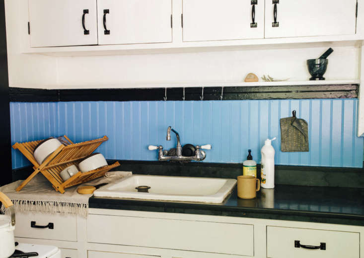 Basic nails and screw hooks above the kitchen sink hold potholders, scrub brushes, and utensils (and won&#8