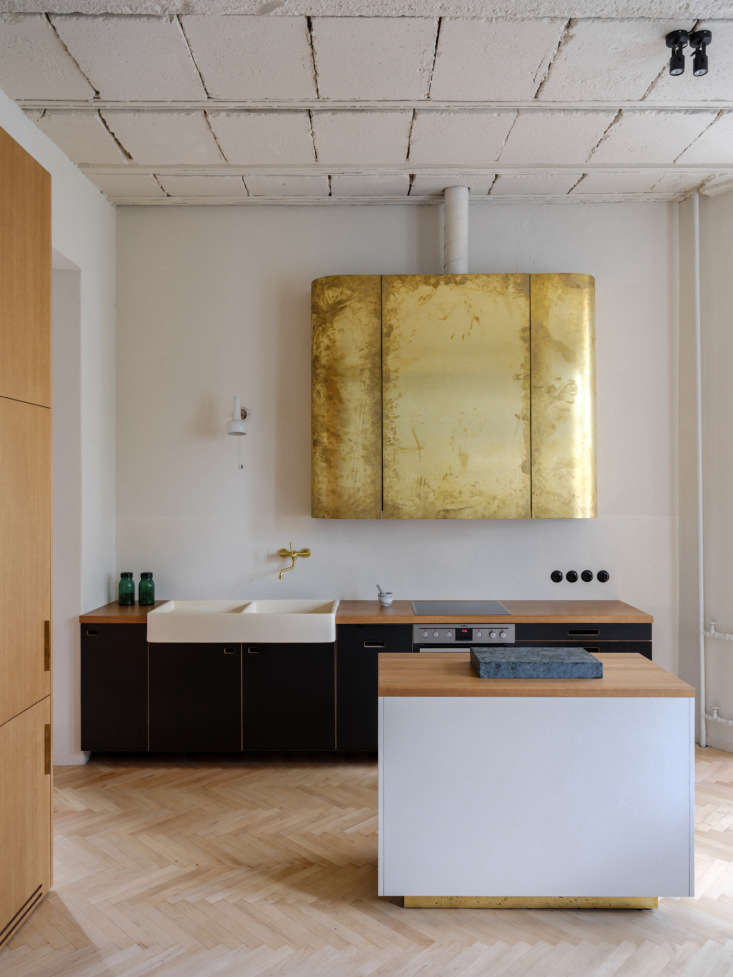 Set in the back of the living space, the kitchen is divided from the rest of the room by a small island that rests on a brass plinth. The brass over the range serves as a vent cover with cabinets flanking it. The fridge and freezer are concealed at the end of the oak cabinet on the left.
