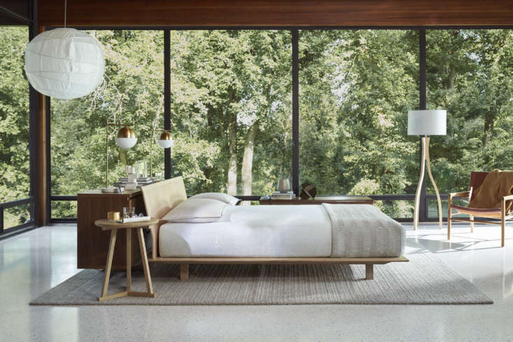 Floor-to-ceiling windows create the illusion of a treehouse bedroom, while the interior materials palette echoes the surrounding landscape.