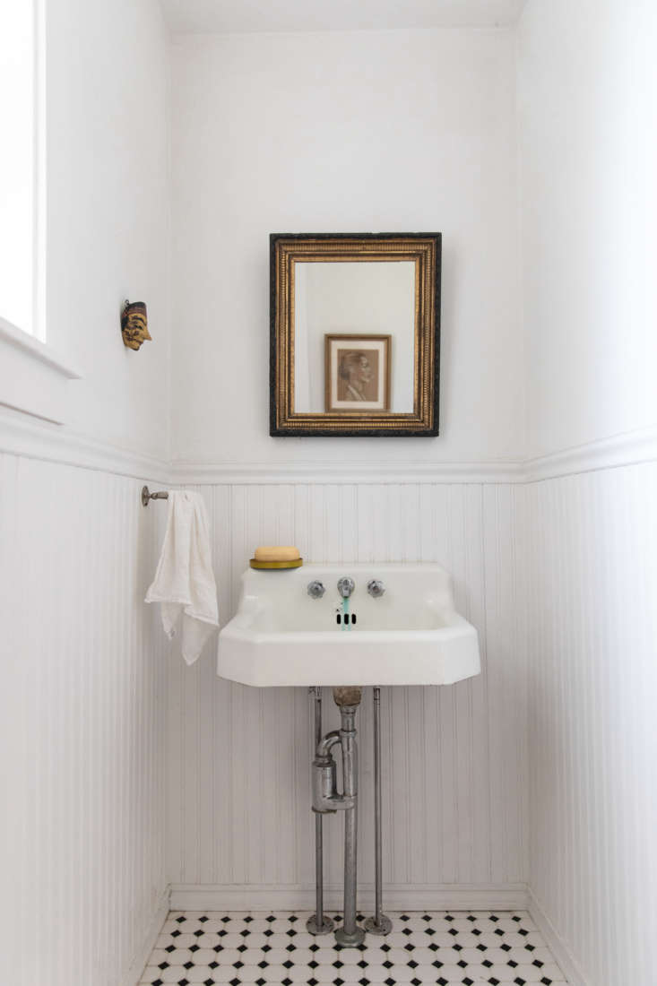 One of two bathrooms, with beadboard wainscoting and a well-loved sink. &#8