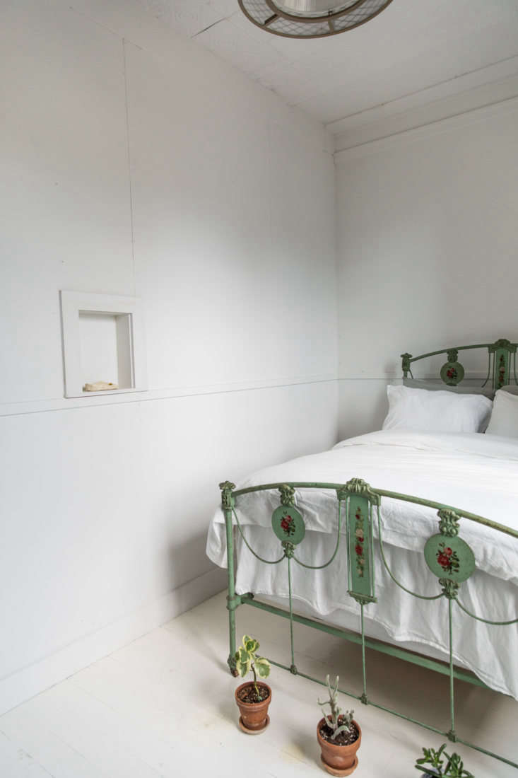 A green-hued bedroom is fitted simply, with a painted iron-frame bed that McNeil found for $75 on Craigslist. She uses the small niche in the wall to display ceramics or dried flowers.