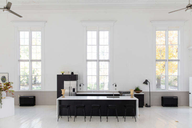 McNeil installed a kitchen in the center of the main space, framed by the windows. Though it looks like a high-end kitchen system, it&#8