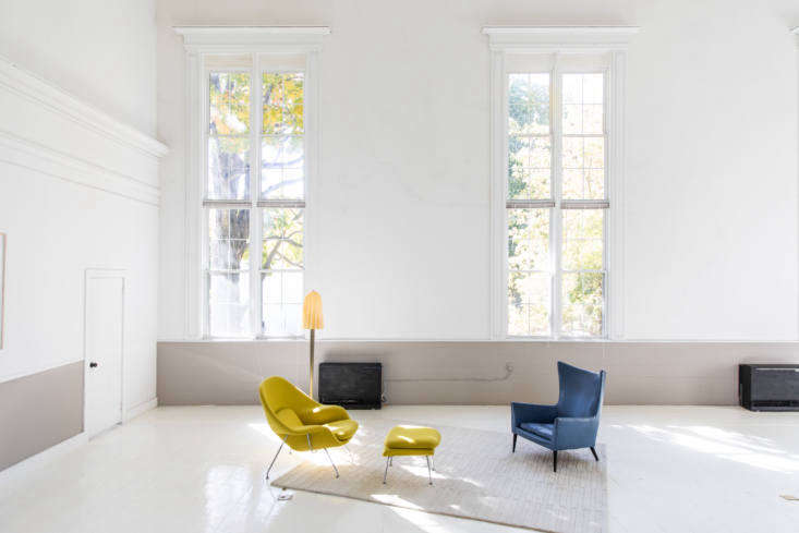 The deconstructed living area is set apart by a rug, and fitted with an Eero Saarinen Womb Chair (&#8