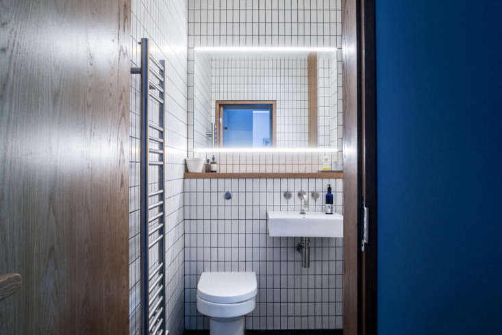 The white tiles and oak detailing reappear in the bathroom located between the kitchen and reception room. That&#8