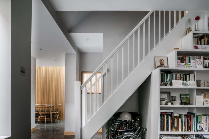 The front hall opens to a small living room with a bookshelf built under the stair, which is one of the few preserved details from the 80s remodel. That&#8