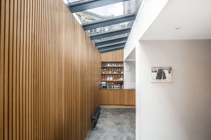 The glass roof extends to the end of the kitchen. Alongside open pantry shelves, an inset wall cabinet holds glassware.