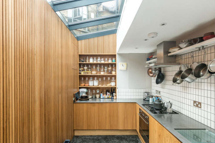 The kitchen cabinets are faced with the same oak used for the slatting. The matte-glazed tiles, sourced from Domus, are set off by dark gray grout. Fridge and freezer are concealed under the counter; the stove and cooktop are by Smeg, and there&#8