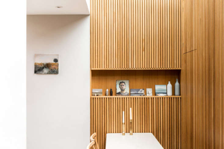 A slot shelf serves as an art display. Drain pipes for the glazed roof are accessible from the door behind the table. &#8