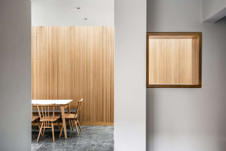 Oak slatted walls introduce pattern and nuance to the space; they&#8