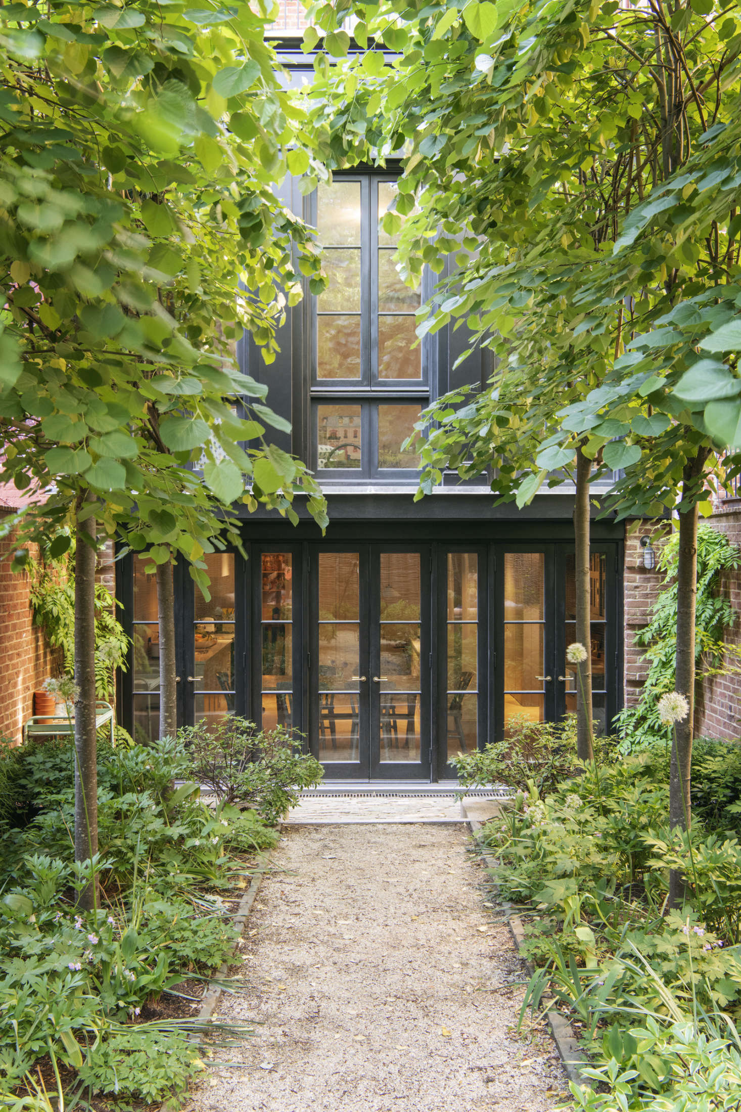 """The house's back addition was modeled after """"the tea porch extensions often introduced to these brownstones in the 50s,"""" says Lekwa. It replaced an existing dilapidated two-story addition, and, Lekwa notes, """"is almost entirely window, but rather than do a huge sheet of glass, we articulated the garden floor with brick piers at the sides. We painted it black just like the old extension.&#8"""