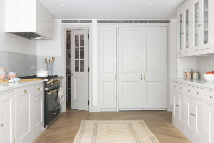 an integrated sub zero double doored fridge in the back of the room is flanked  19