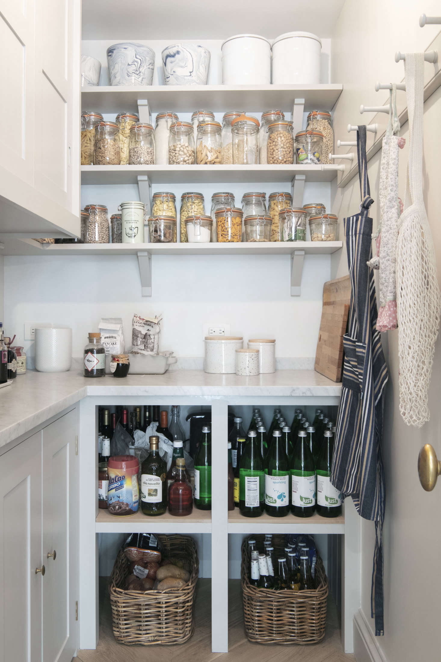 A proper pantry with a marble counter and a peg rail for shopping bags and aprons. Dry goods are decanted into Le Parfait Jars. The upper cabinets hold the microwave and coffee machine; bakeware is stowed in the lower ones.