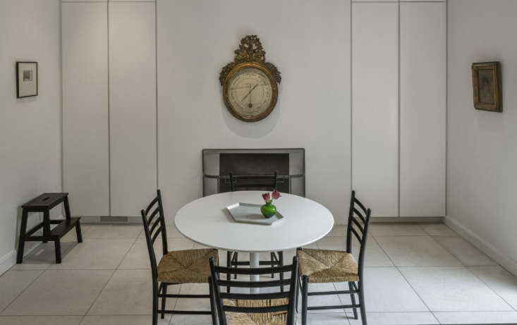 The kitchen table came from West Elm and the rush chairs are a vintage Gio Ponti design that Mahlow bought on eBay. The fireplace replaced a space-hogging brick original; the new setup has a gas insert and is flanked by seamless storage cabinets. The carved-wood clock is Belgian.